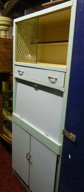 A Vintage Freestanding Kitchen Cabinet Enclosed By An