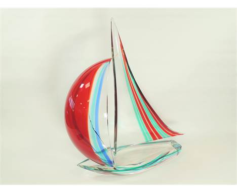 An Italian Murano glass sculpture of a sailing boat, with encased red, blue and green colouration, the base with inscribed ar