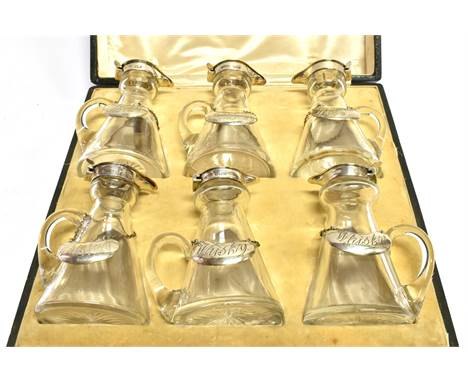 SIX SILVER MOUNTED CLEAR-GLASS CONICAL WHISKY NOGGINS AND SIX 'WHISKEY' LABELS  each glass noggin with a star-cut base and a