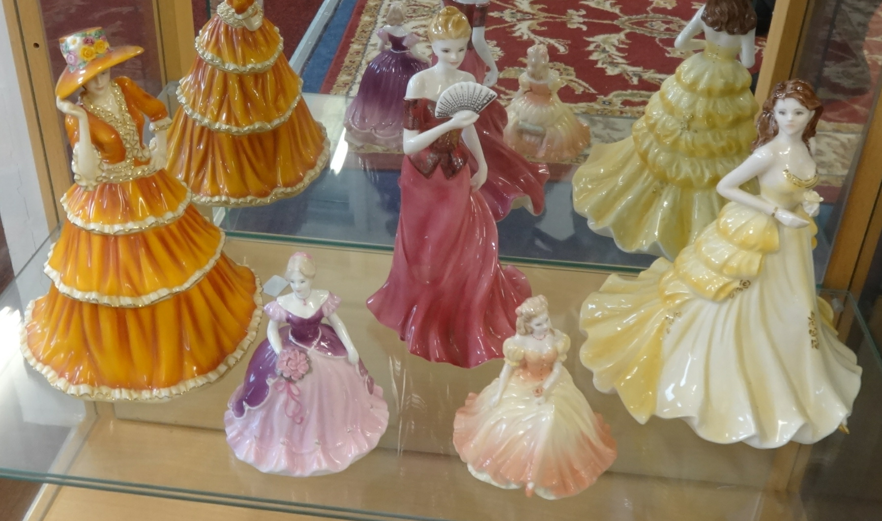 Lot 042 - A collection of 19 porcelain figurines including Coalport, Doulton Pretty Ladies series and