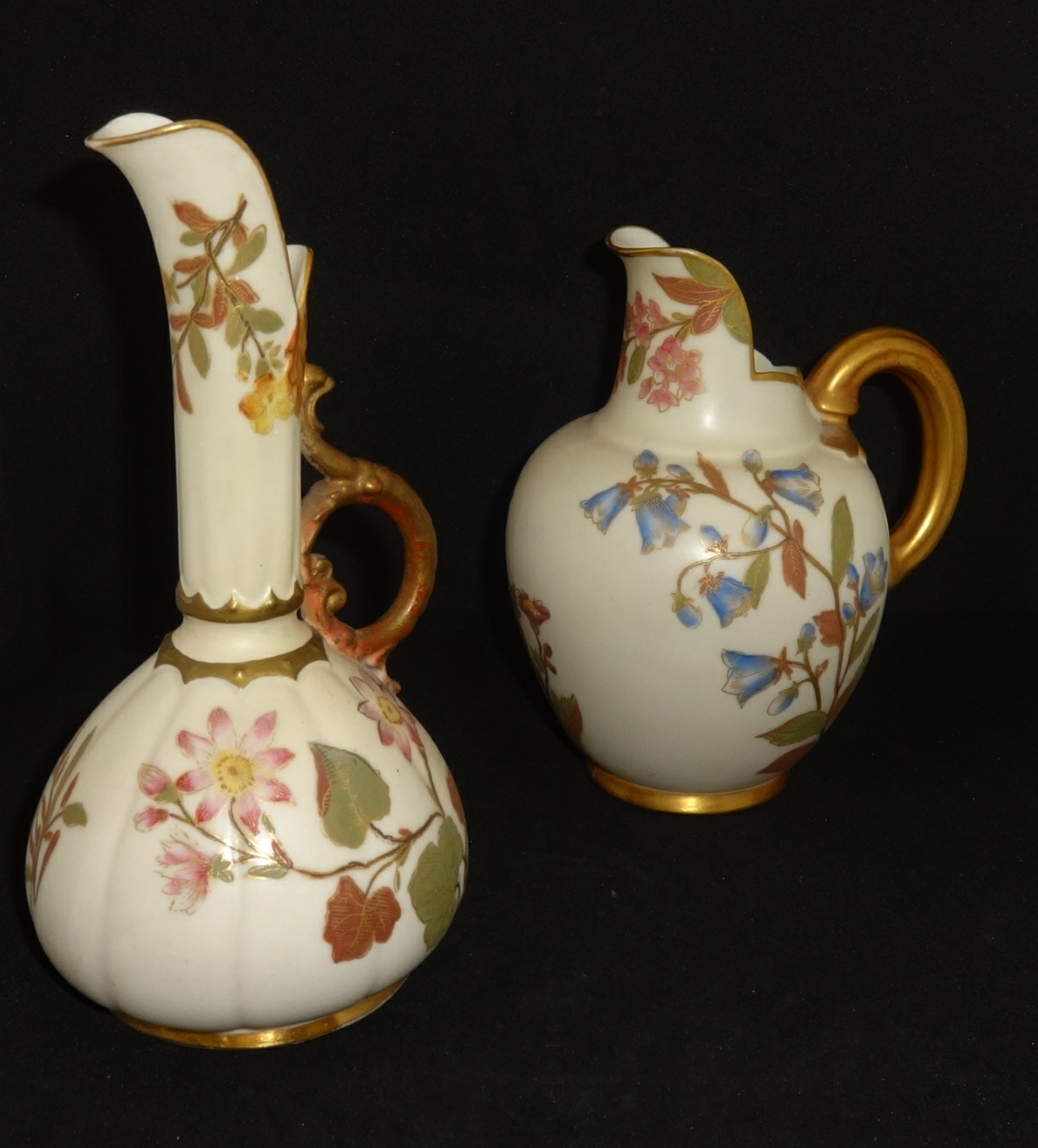 Lot 045 - Royal Worcester, two blush ivory jugs decorated with wild flowers, the tallest 16cm.