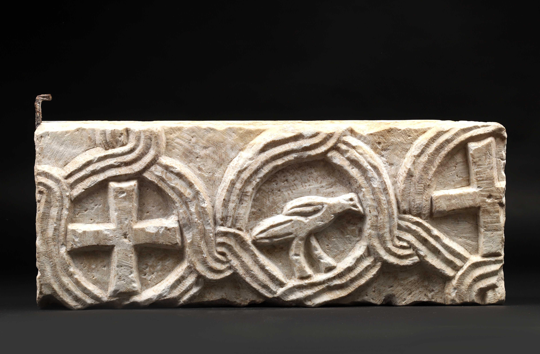 Plaque en marbre blanc sculptée en bas-relief sur une face d'un entrelacs avec [...]
