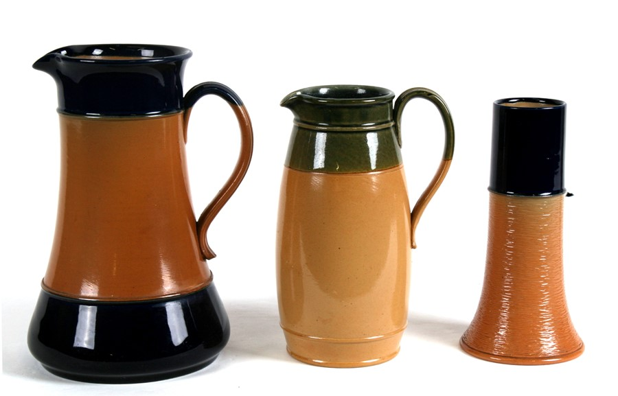 Two Royal Doulton Stoneware jugs, the largest,24cms (9.5ins) high; together with a similar vase,