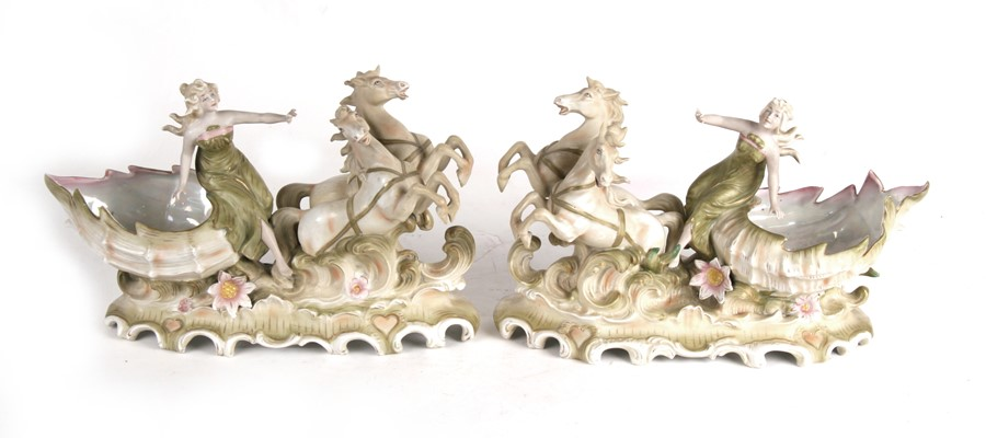 A pair of Royal Dux style Art Nouveau porcelain baskets in the form of a maiden being pulled along