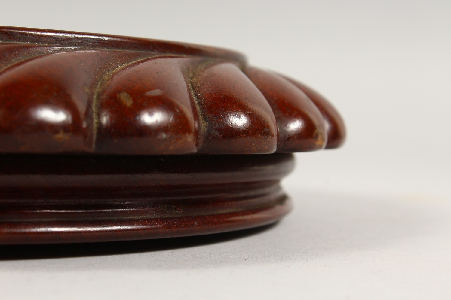 Lot 1430 - A 19TH CENTURY TURNED AND CARVED MAHOGANY CIRCULAR CHEESE COASTER/STAND, on three brass and mahogany