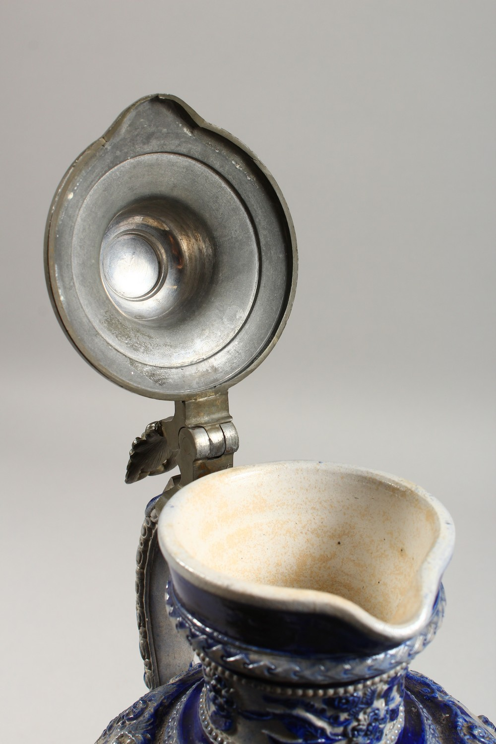 Lot 1150 - A CONTINENTAL STONEWARE JUG, with blue glazed, moulded decoration and pewter lid. 13ins high.