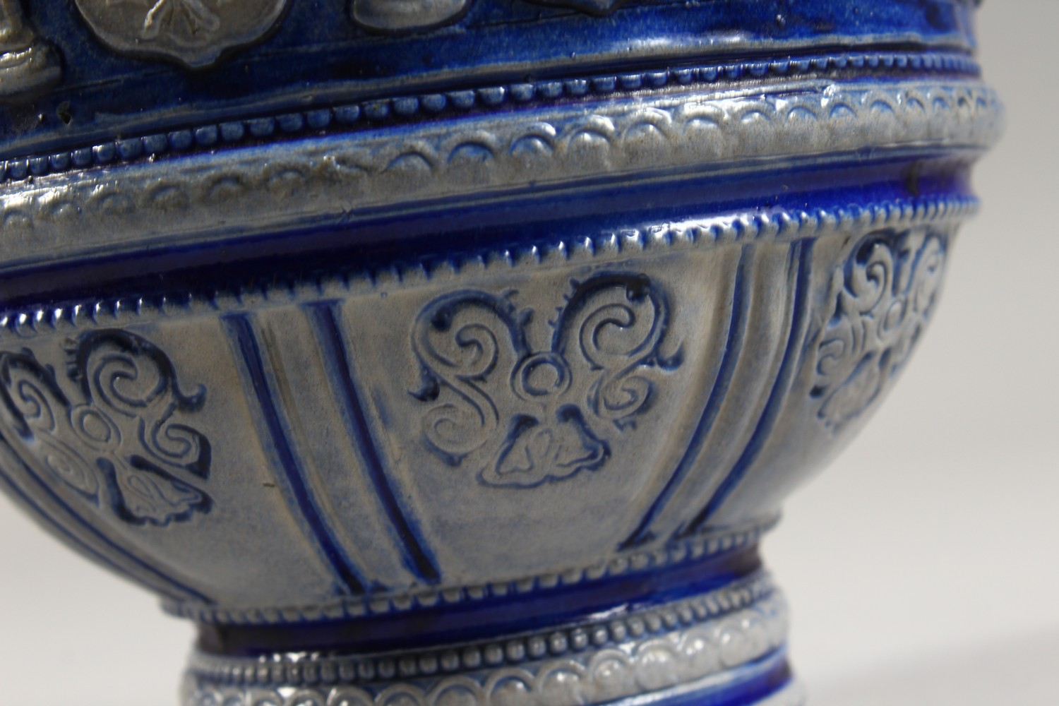 Lot 1151 - A CONTINENTAL STONEWARE JUG, with blue glazed, moulded decoration and pewter lid. 13ins high.