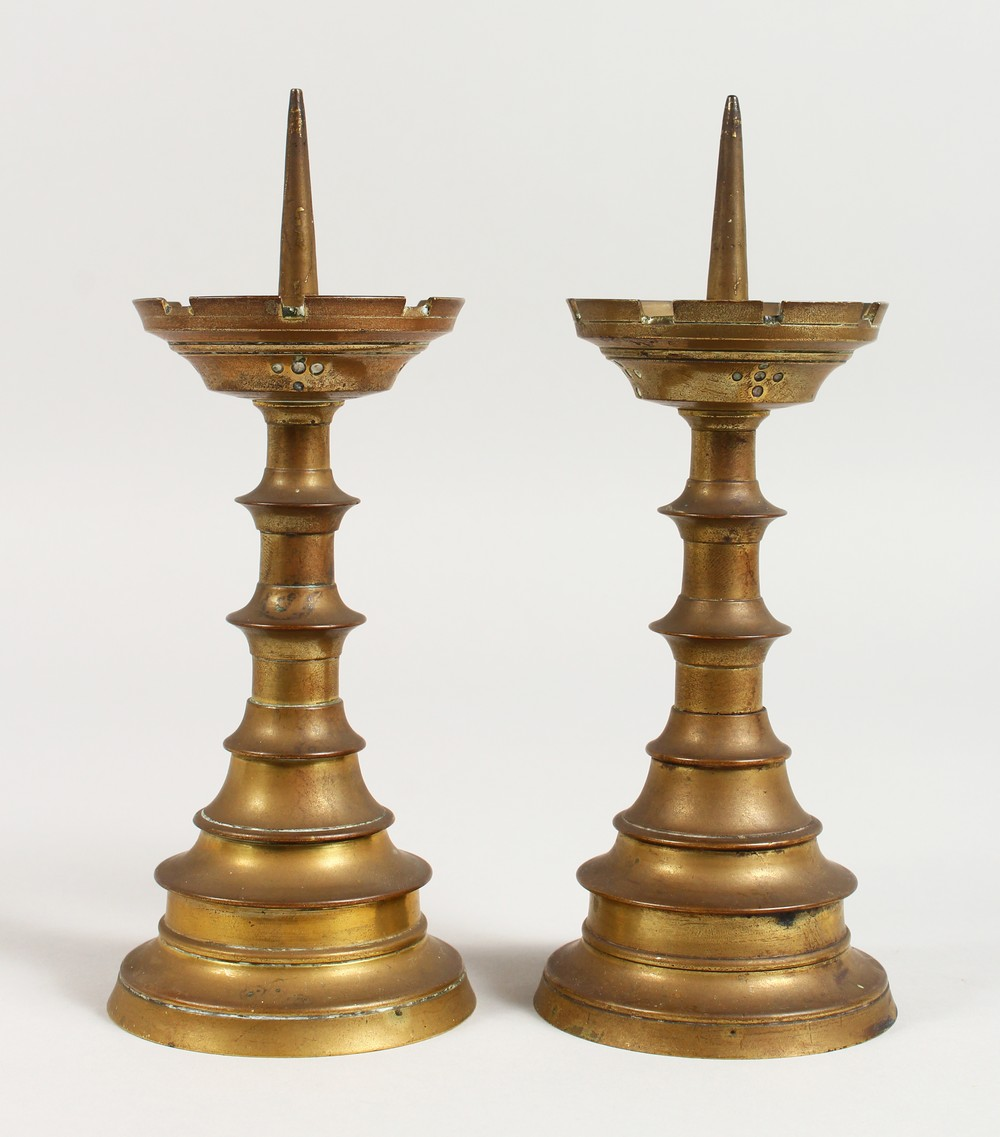 Lot 1514 - A PAIR OF TURNED BRASS CANDLESTICK, with castellated drip pans. 8ins high.