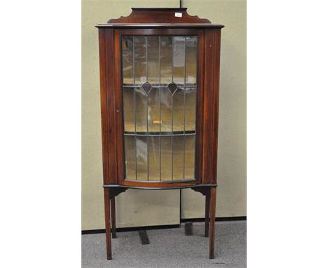 A late 19th/early 20th century mahogany glazed display cabinet with stained glass motif to the front panels, inlaid detail th