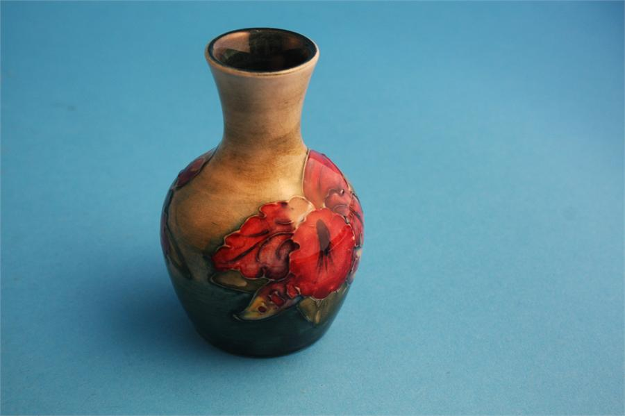 """Lot 28 - A small Moorcroft vase decorated with """"Hibiscus"""" on mottled green ground, impressed mark.  9 cm"""