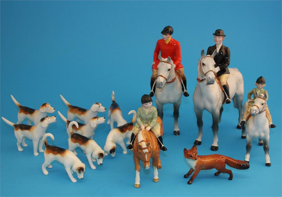 Lot 26 - A Beswick hunting group comprising huntsman and huntswoman on dappled grey horses, a boy on a