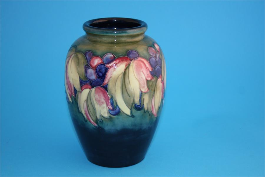 "Lot 24 - A Moorcroft ovoid shape vase ""leaf and berry"" pattern in a graduated green and blue ground."