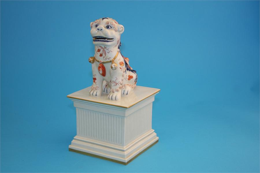 Lot 13 - A Chinese Dog of Fo supported on a large square plinth base. 28 cm high.  14 cm wide.