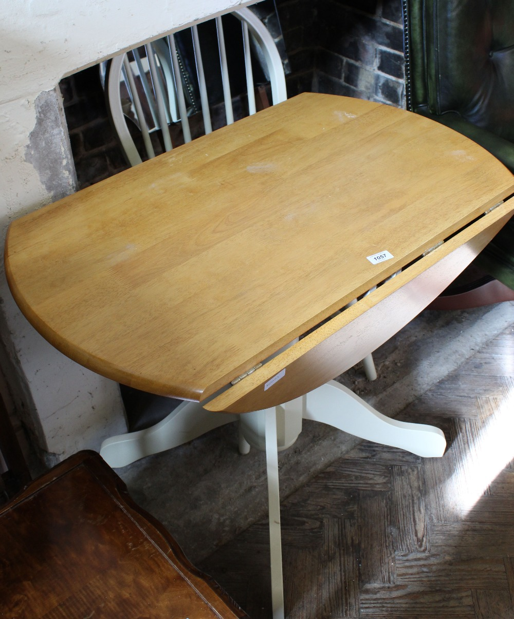 Lot 1057 - A modern pine and cream painted drop leaf pedestal table and a chair