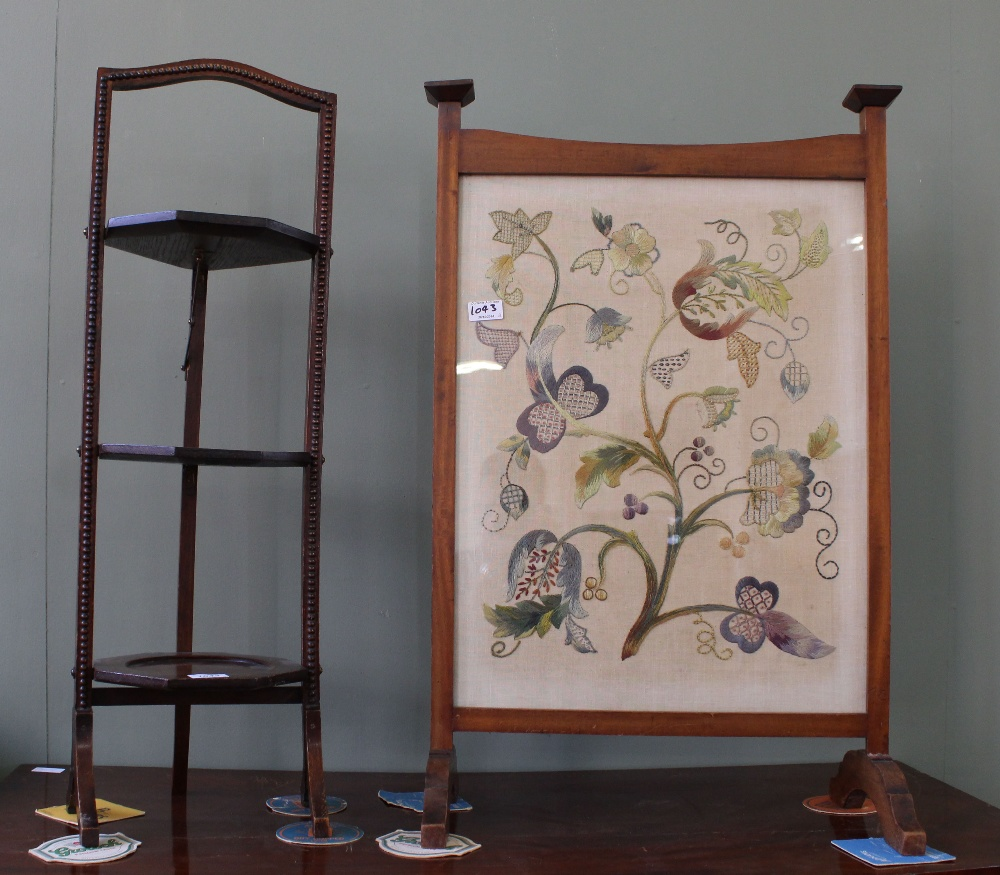 Lot 1043 - A folding oak cake stand and a crewel embroidery decorated fire screen