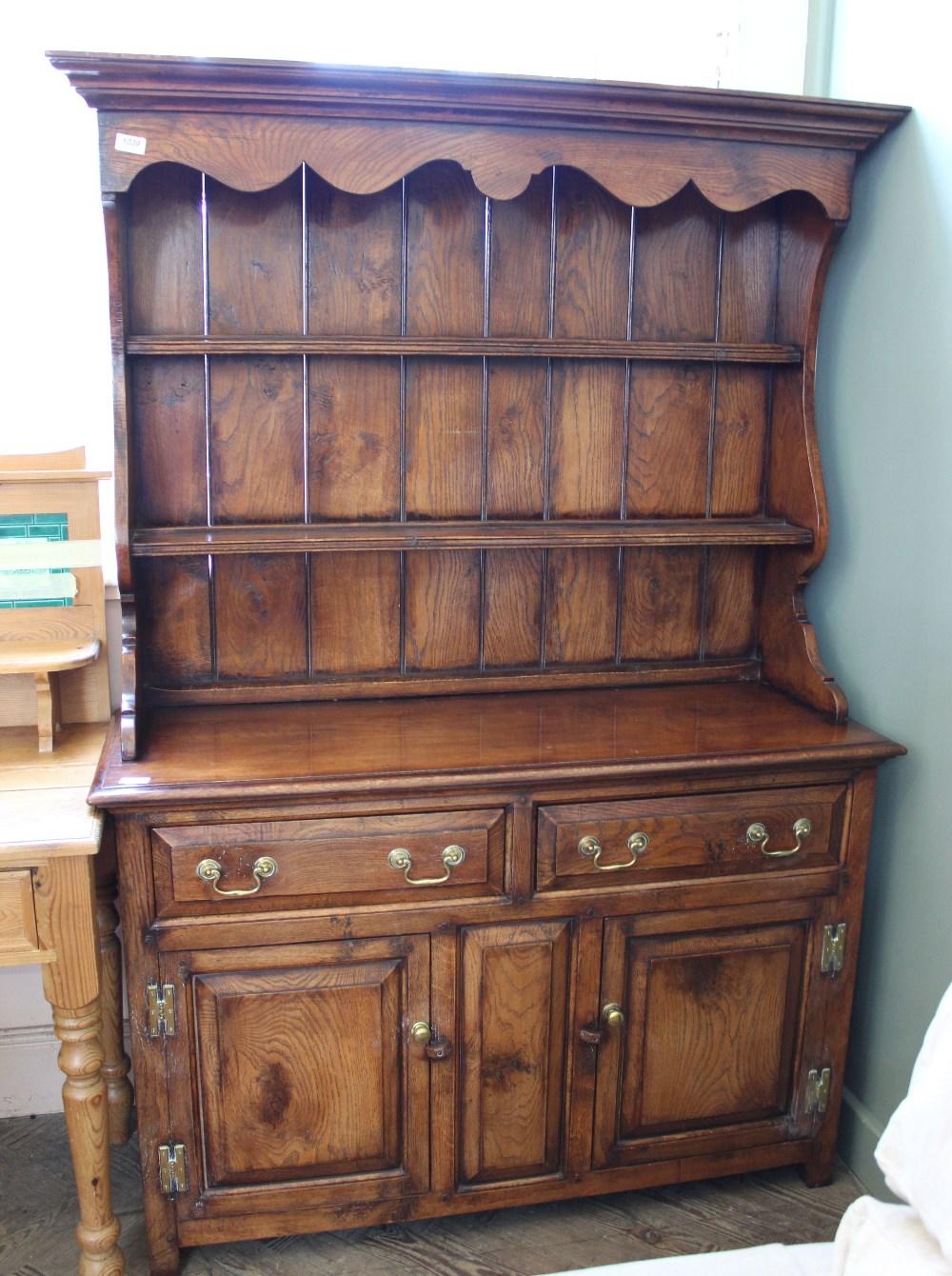 Lot 1039 - A shelf back oak kitchen dresser with brass hardwear