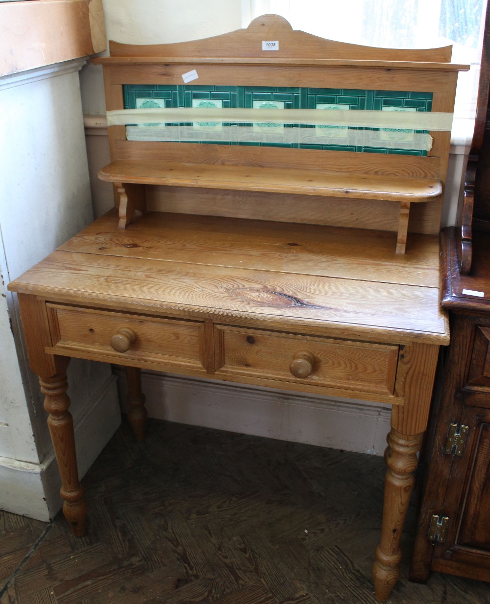 Lot 1038 - A reproduction pine two drawer washstand with green tiled upstand