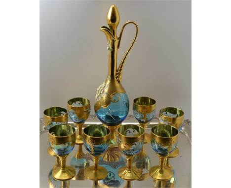 A 20TH CENTURY BOHEMIAN GLASS WINE DECANTER AND A SET OF EIGHT STEMMED GLASSES, blue tinted, heavily gilded and floral encrus