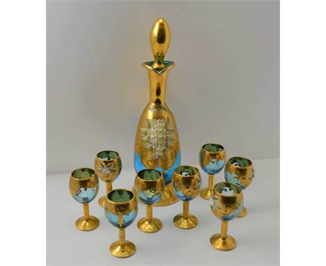 A 20TH CENTURY BOHEMIAN GLASS LIQUEUR DECANTER AND A SET OF EIGHT STEMMED GLASSES, blue tinted, heavily gilded and floral enc