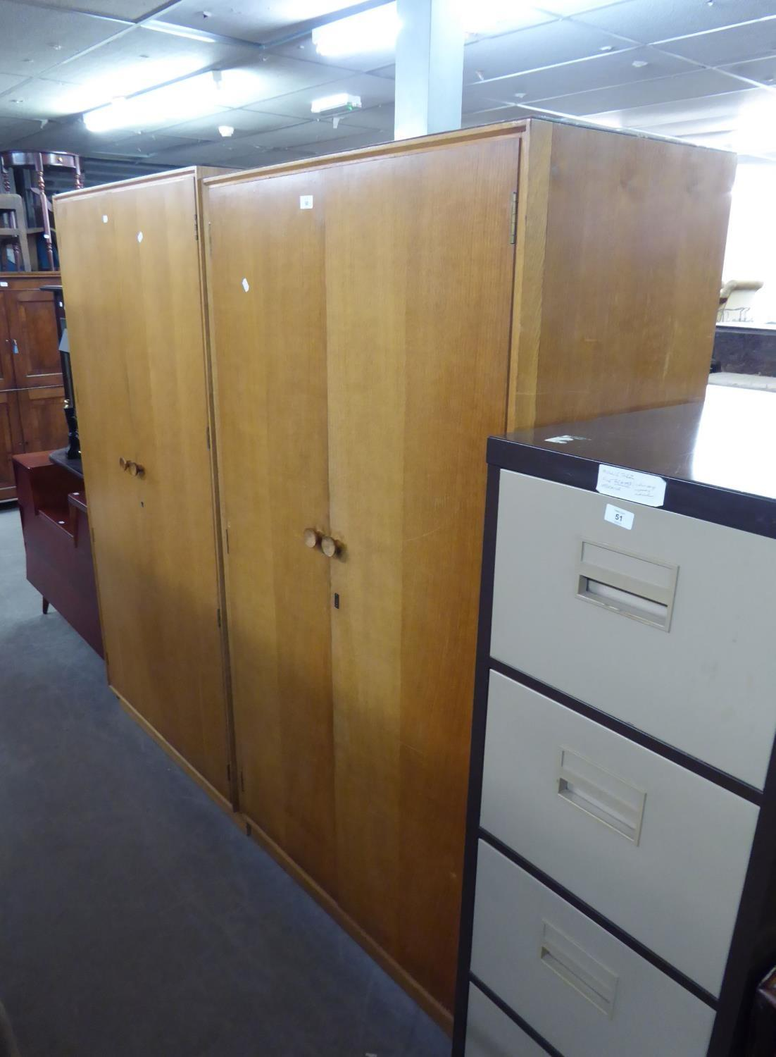 A PAIR OF 1950's LIGHT OAK TWO DOOR WARDROBES AND A SUNK CENTRE DRESSING TABLE (LACKS MIRRORS (3)