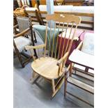 A LIGHT OAK ROCKING CHAIR WITH SPINDLE BACK AND ARMS