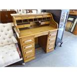 EDWARDIAN OAK ROLL TOP KNEEHOLE DESK, THE ENCLOSED TOP REVEALING FITTED COMPARTMENTS OVER A BASE