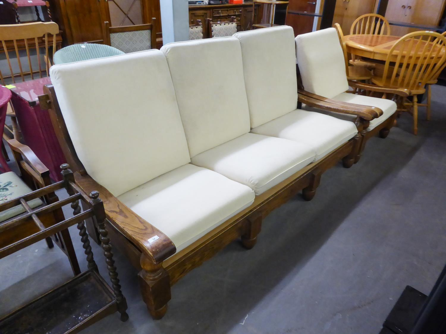 AN OAK FRAMED THREE SEATER SETTEE AND MATCHING LOUNGE ARMCHAIR, WITH LOOSE BACK AND SEAT CUSHIONS