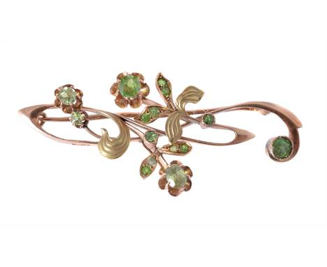 An early 20th century demantoid garnet Russian Art nouveau brooch, the two colour floral whiplash motif brooch set with circu