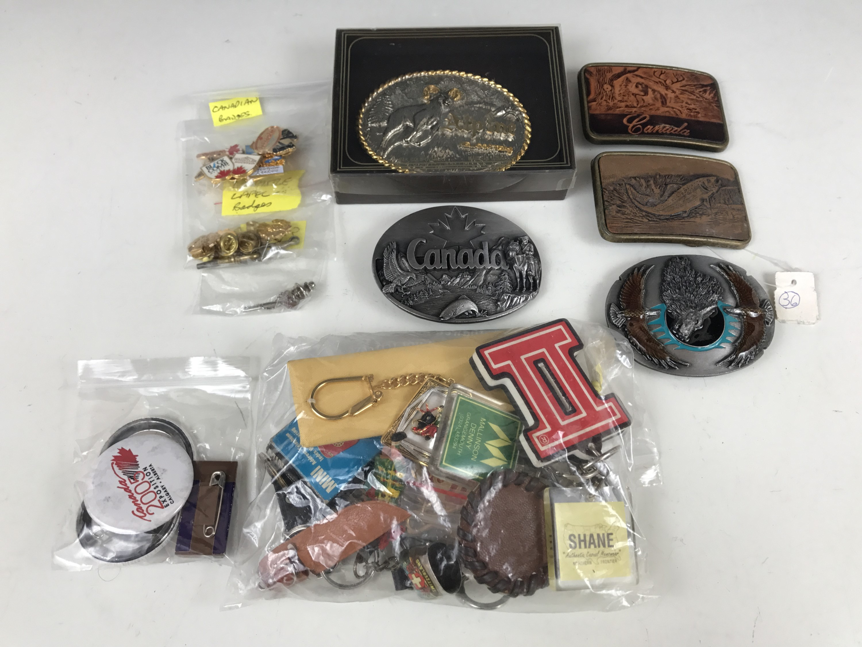 Lot 33 - Four Canadian belt buckles together with a quantity of key rings and lapel badges etc