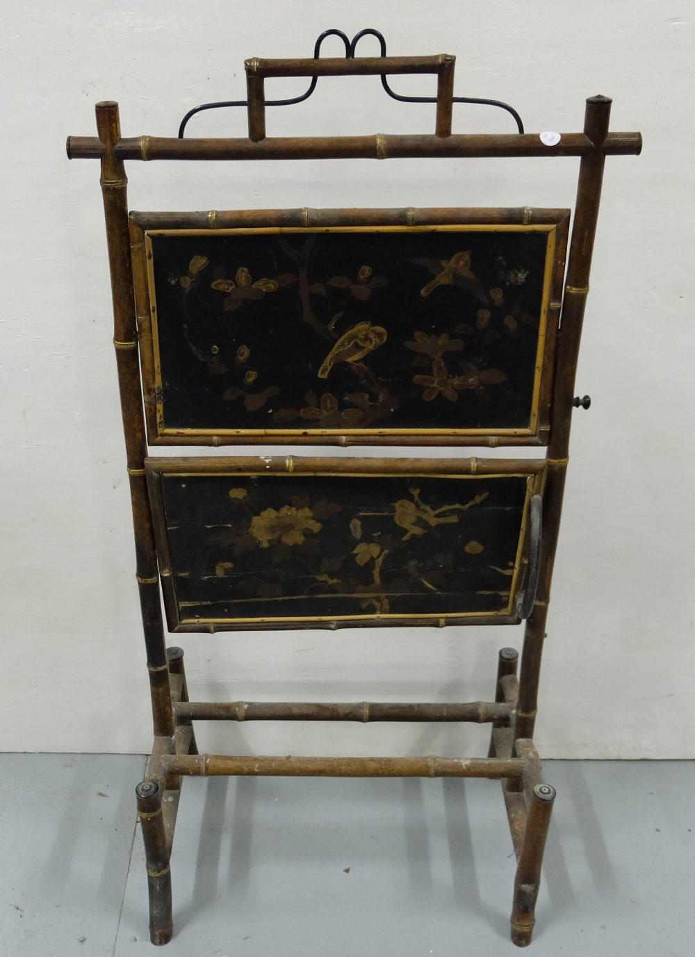 "Lot 23 - Victorian Bamboo Framed and Chinese Lacquered Covered Fire Screen with a folding shelf, 19""w x 40""h"