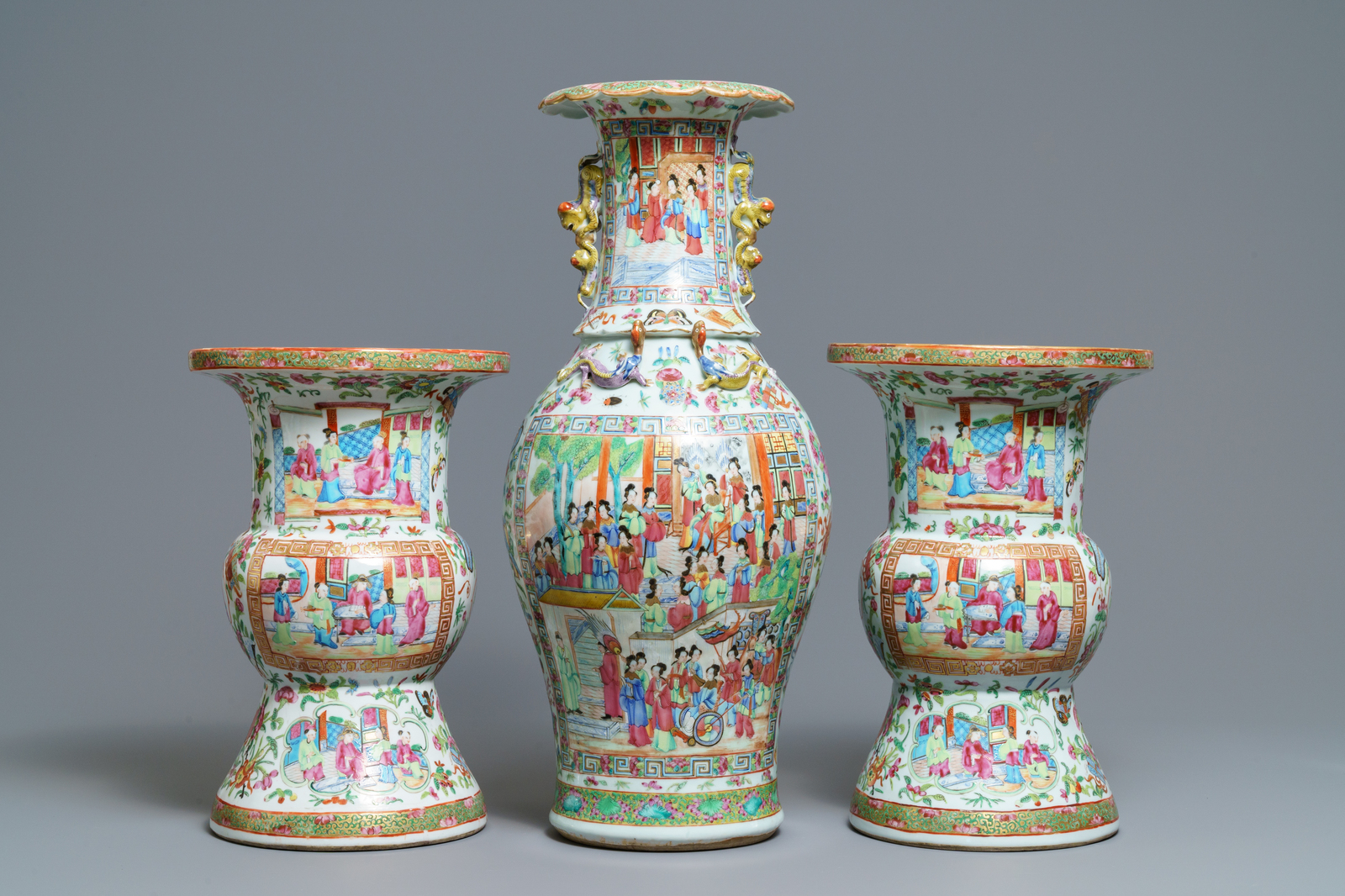 A pair of Chinese Canton famille rose spittoons and a vase, 19th C.