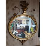 A Regency carved giltwood mirror, with eagle and floral surmount, having oval glass plate, 100