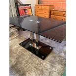Black glass top table on twin chrome pedestal.