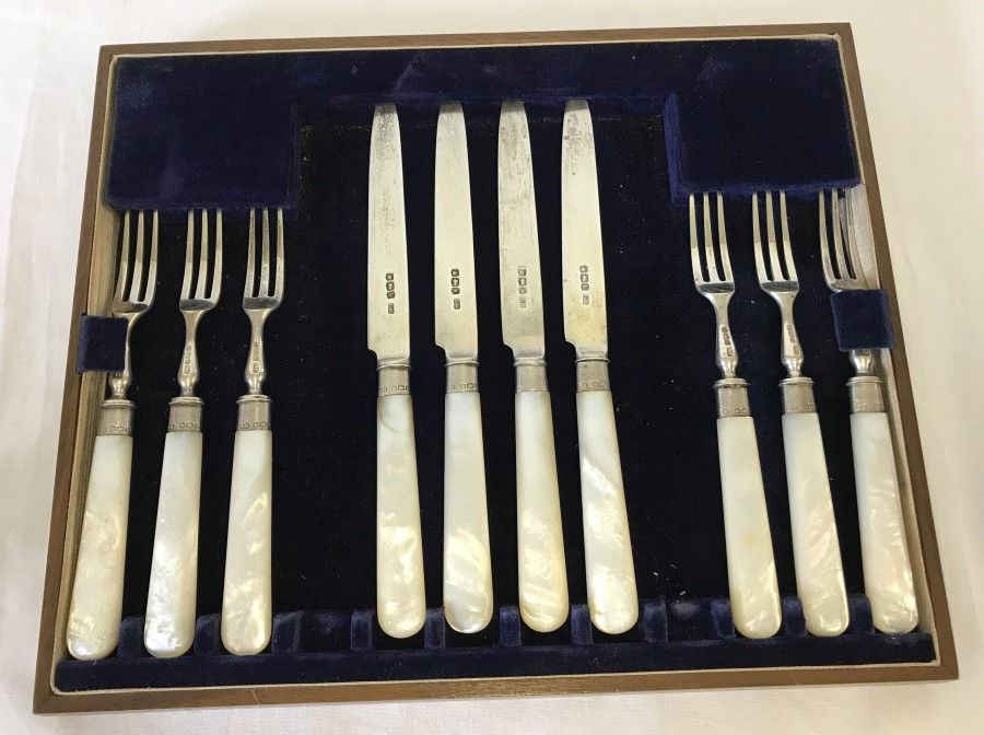 Lot 241 - A boxed set of silver bladed fruit forks and knives with mother of pearl handles and silver mounts.