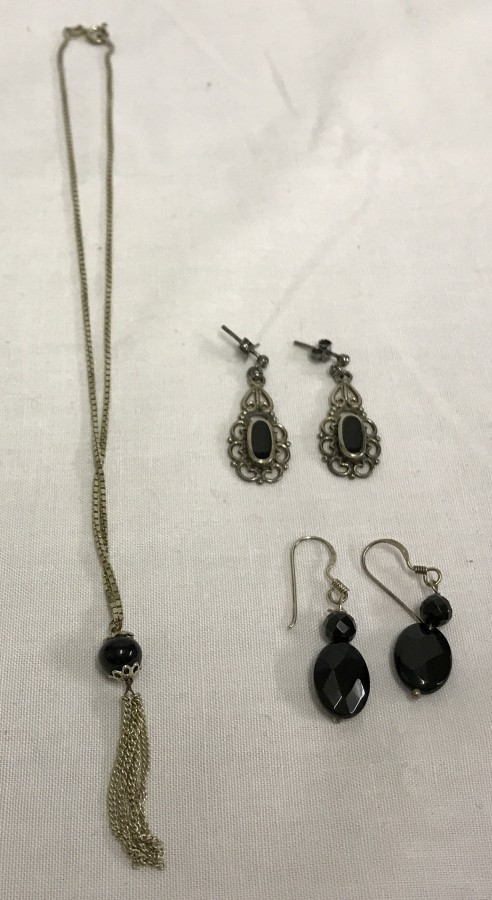 Lot 168 - 2 pairs of silver earrings together with a silver necklace, all set with black stones.