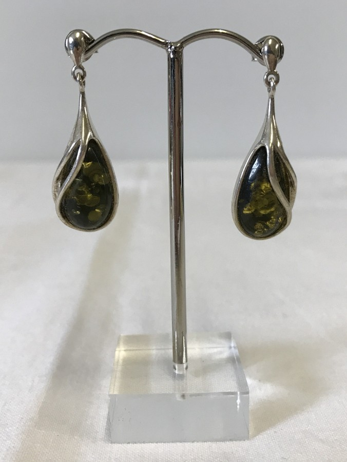 Lot 143 - A boxed pair of green amber & silver drop earrings.