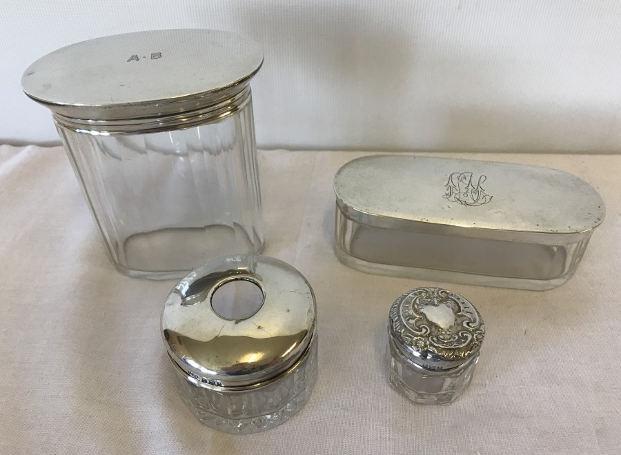 Lot 213 - 4 silver topped vanity jars.
