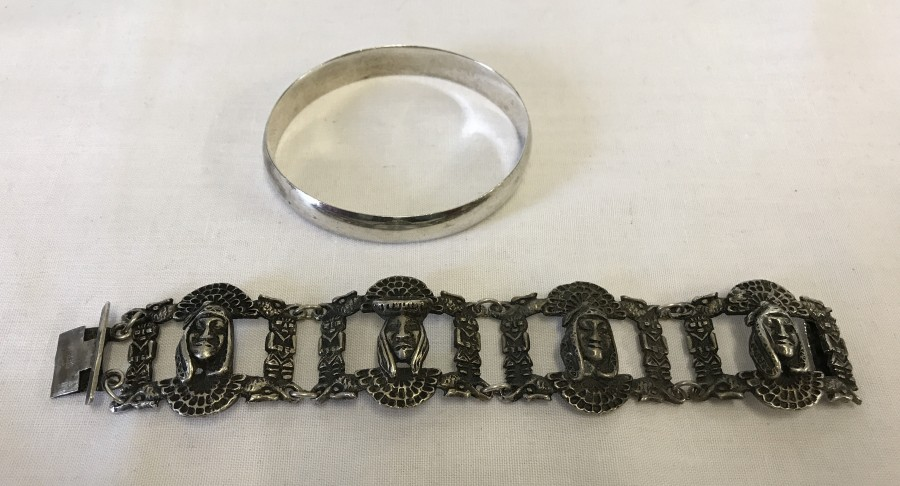 Lot 37 - A solid Sterling silver bangle, together with a silver bracelet with Aztec design.