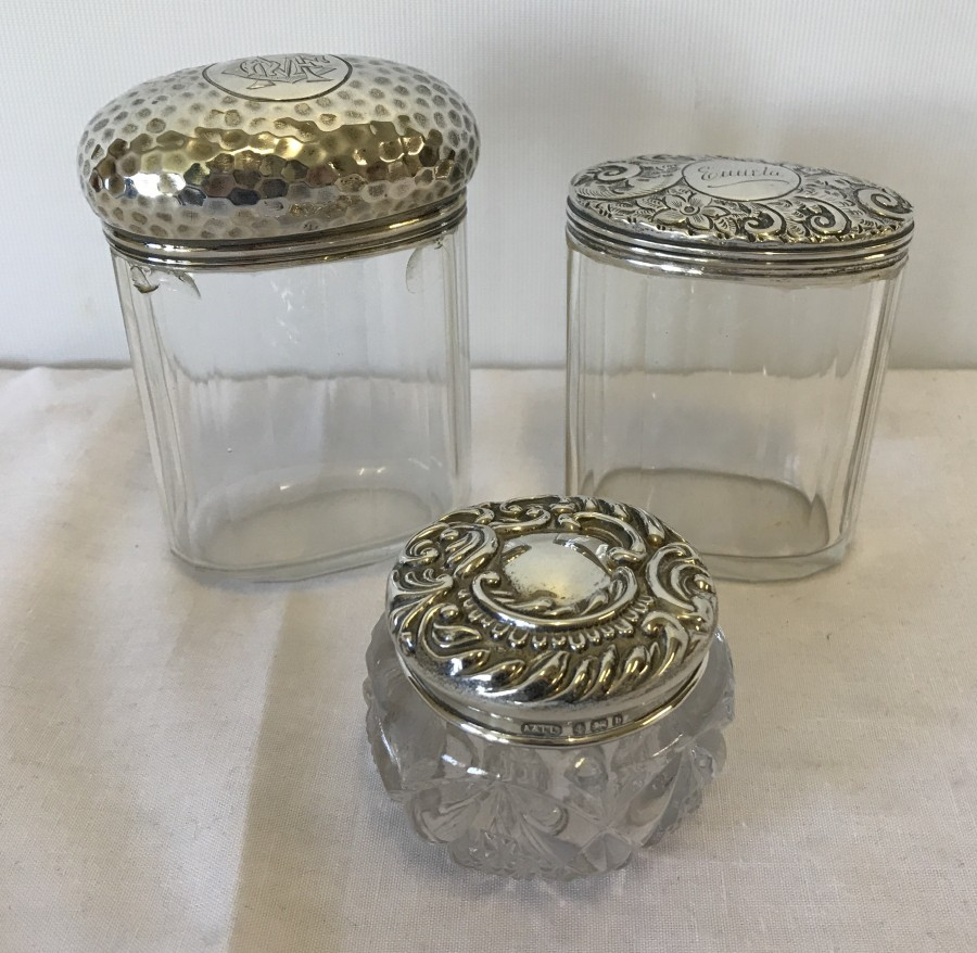 Lot 212 - 3 silver topped vanity jars.