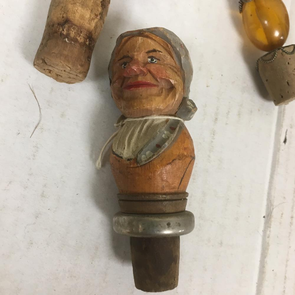 Lot 306 - A COLLECTION OF NOVELTY BOTTLE STOPPERS, INCLUDING THREE WHITE METAL EXAMPLES, THREE CARVED WOODEN