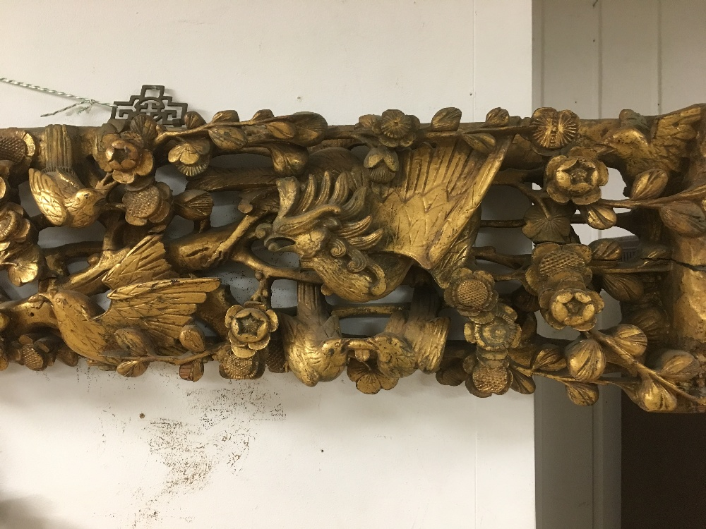 Lot 422 - A CARVED WOODEN GILT WALL PLAQUE OF BIRDS AMONGST FOLIAGE, 145CM WIDE