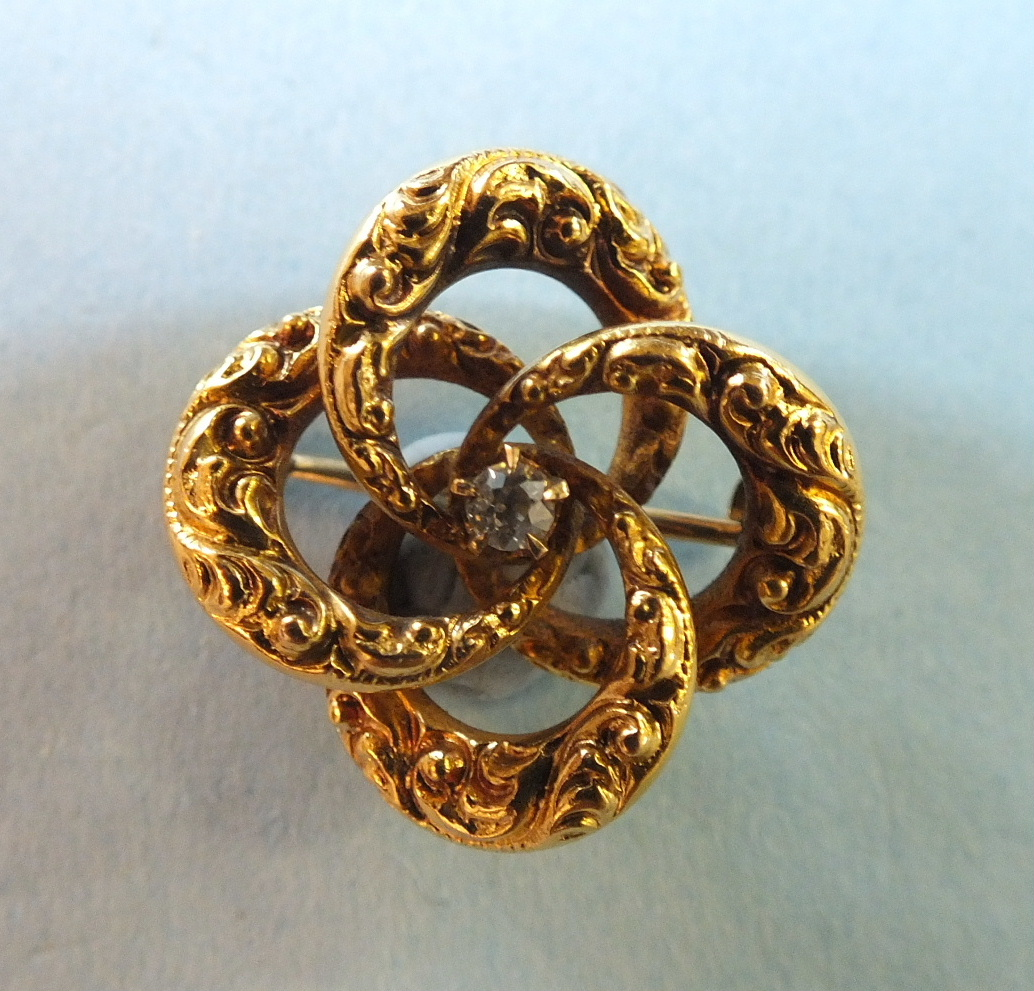 Lot 172 - A 14k gold brooch of four linked rings centred by a brilliant-cut diamond, 2cm diameter, 3g.
