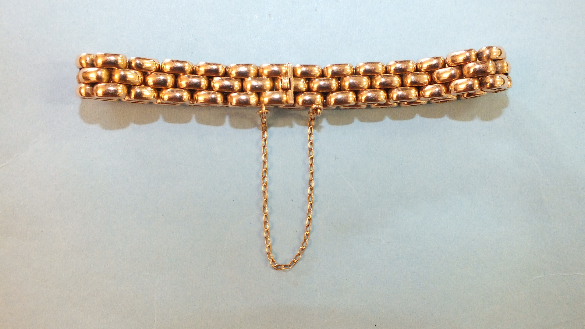 Lot 219 - A rose gold bracelet of rounded brick links with concealed clasp and safety chain, 26.5g.