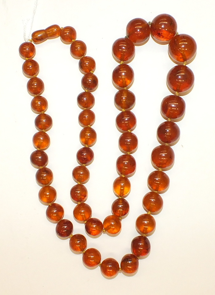 Lot 181 - A single row of 47 graduated spherical honey-coloured amber beads, smallest 11mm, largest 19mm, 72.