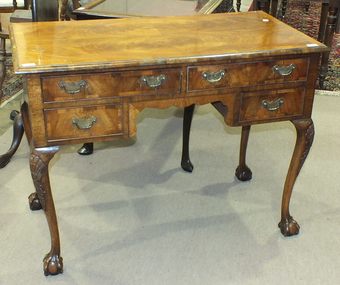 Lot 54 - A cross-banded walnut dressing table in the early-18th century style, the rectangular top above an