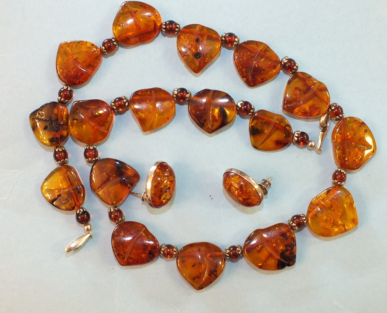 Lot 179 - An amber necklace of seventeen leaf-shaped plaques, (one with small fly inclusion), with amber beads