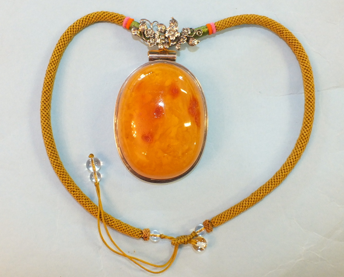Lot 216 - A large butterscotch amber pendant mounted in white metal on plaited necklet with white metal floral