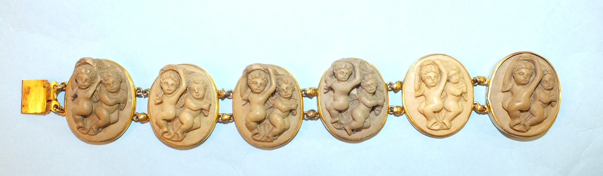 Lot 205 - A 19th century lava bracelet of six plaques, each carved in high relief with two infants, in gilt