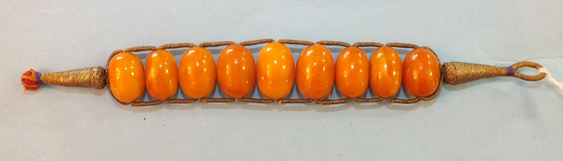 Lot 180 - An ethnic amber bracelet of nine graduated amber beads on metallic thread mount, 17cm, 16.7g.