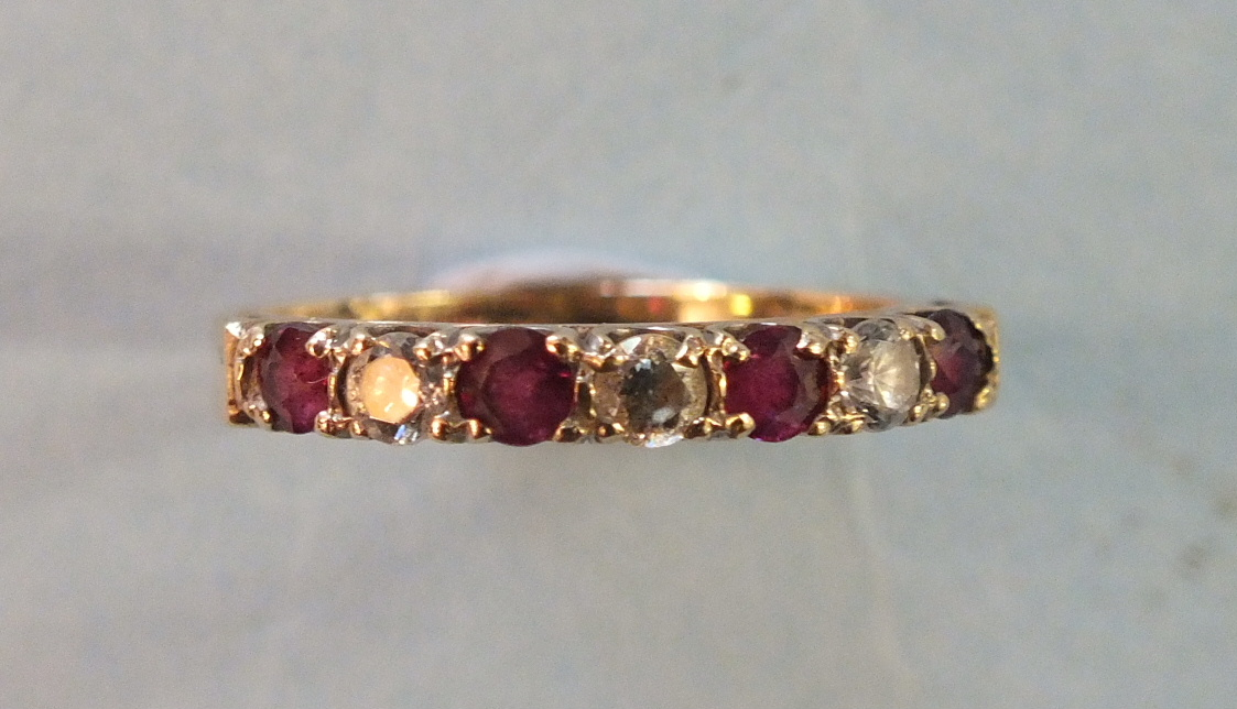 Lot 168 - A ruby and diamond half-hoop ring claw-set three brilliant-cut diamonds, set alternately with four
